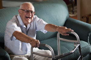 Senior man (80s) laughing, getting up from couch, using walker.
