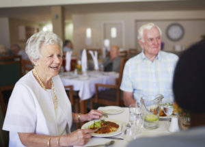 Elderly smiling lady talking to friends at lunch in their old age home