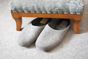 old grey slippers on carpet with stool