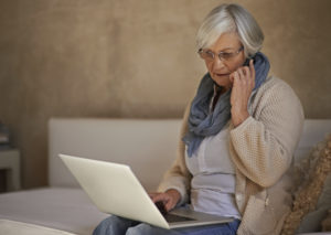 A senior woman on her mobile while using her laptop at home
